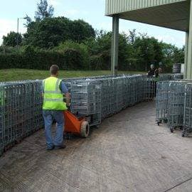 Electric tug moving dairy roll cages
